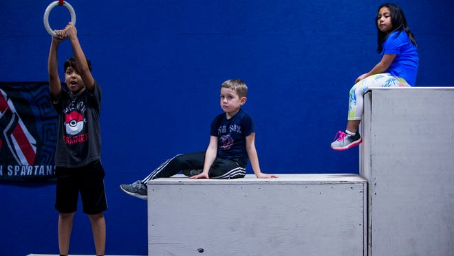 From left, a student, Jack Shaw and Izabelle Bilon listen to Coach Storm Sims teach them ring exercises during a training class at Total Obstacle Course Training on January 25, 2018.