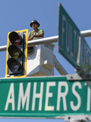 Workers from Perran Electric, of Wadsworth, align new traffic signals at the corner of Fulton Drive and Amherst Avenue NW in Jackson Township.