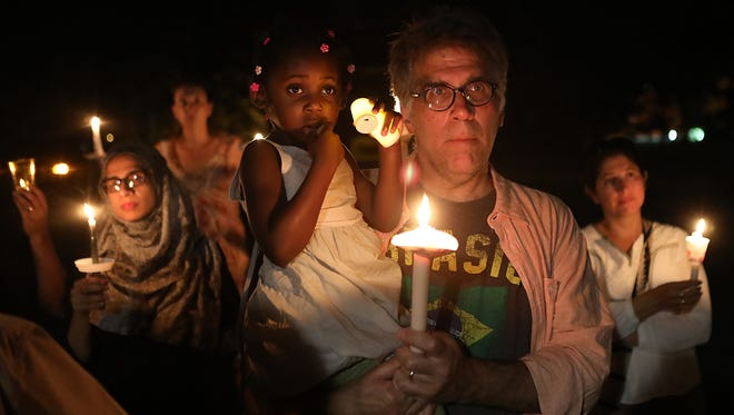 Mark Desiderio holds his daughter Olivia as they participate in a vigil held for the victims of the attack in Charlottesville, V.A. in Teaneck, N.J. on Sunday, August 13, 2017.