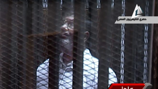 In this image taken from Egyptian state TV,  toppled president Mohammed Morsi stands inside a glass-encased metal cage in a courtroom in Cairo on Tuesday.