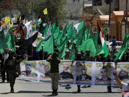 Masked militants from the Izzedine al-Qassam Brigades, a military wing of Hamas, hold posters of people held at Israeli jails and waving their party flags during a rally marking Palestinian Prisoners Day in Gaza City, Monday, April 17, 2017. An activist said more than 1,500 Palestinian prisoners have launched an open-ended hunger strike to demand better conditions in Israeli prisons, including more contact with relatives, and an end to Israel's practice of detentions without trial.