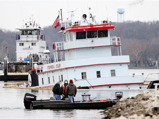 Officials inspect the Stephen L. Colby, which took on water after striking a submerged object in the Mississippi River off Le Claire. The river was closed for a time to barge traffic but has been reopened.