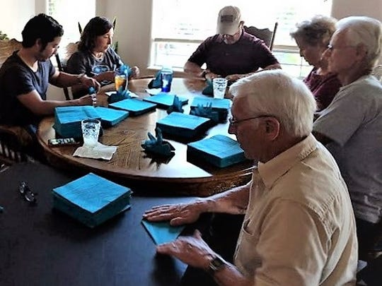 Flickinger Guild members and volunteers fold napkins for the group's Turquoise and Tea event Oct. 15.