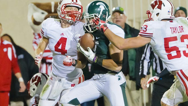 Keith Nichol (center) secures a Hail Mary pass between two Wisconsin defenders at the Wisconsin goal line with no time left on the clock on Oct. 22, 2011.