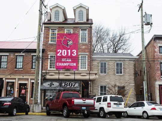 "A replica of the 2013 NCAA national Championship basketball banner hangs from the front of Taj Louisville, a bar on Market Street and Shelby. Owner Todd Moore says, ""when we got notice that they were going to take the banner down, we got this one. They can't take this one so we're going to have one in town still."""