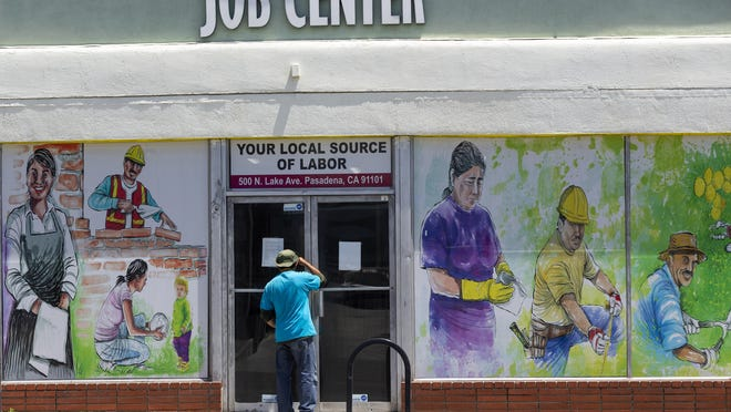 FILE - In this May 7, 2020 file photo, a person looks inside the closed doors of the Pasadena Community Job Center in Pasadena, Calif., during the coronavirus outbreak. California's unemployment rate continued to climb in May, reaching 16.3% as businesses continued to lay people off because of a state-at-home order aimed at slowing the spread of the coronavirus that has wrecked the state's economy. It's the highest unemployment for the nation's most populous state since the Great Depression.