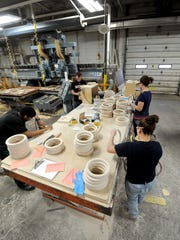 Workers at Cooper Enterprises sand rings used for athletic equipment.