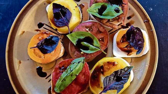 A mix of purple and green basil and a balsamic reduction atop pieces of caprese and different colored tomatoes makes a more colorful plate.