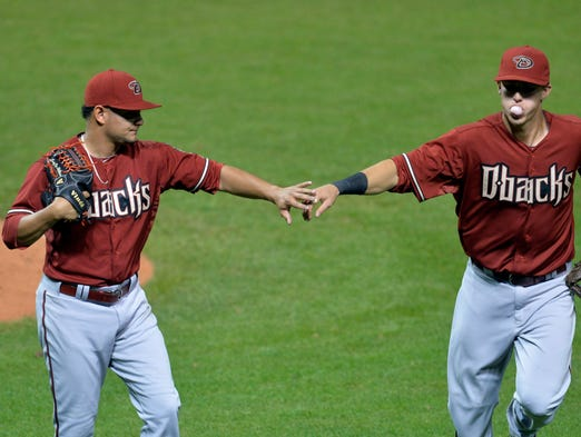 Aug 13, 2014; Cleveland, OH, USA; Arizona Diamondbacks relief pitcher Eury De La Rosa (left) and third baseman Jake Lamb (19) celebrate in the sixth inning after completing a double play against the Cleveland Indians at Progressive Field.