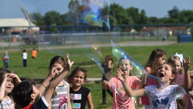 Mountain Home Kindergarten students enjoy big bubbles Wednesday on their last day of school.