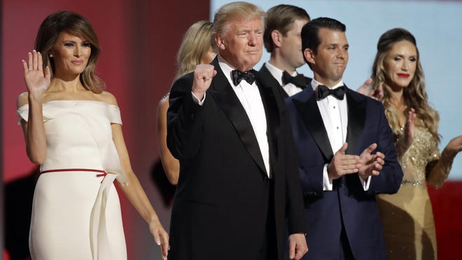 In this Jan. 20, 2017, file photo President Donald Trump, center, raises his fist alongside first lady Melania Trump, left, and son Donald Trump, Jr., after dancing at the Liberty Ball following his inauguration in Washington.