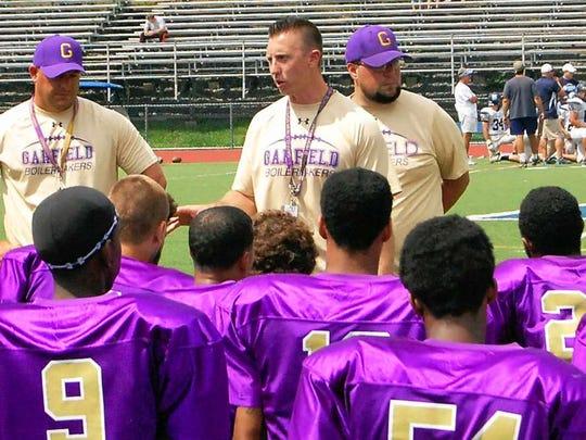 Garfield High School football coach Jeff DeVito (center) has a young squad this season.