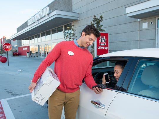 A Target employee bringing an order to a customer's car curbside.