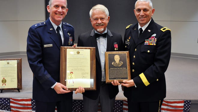 Maj. Gen. Don Dunbar, Wisconsin's adjutant general, and Brig. Gen. Mark Anderson, Wisconsin's deputy adjutant general for Army, present a proclamation from Gov. Scott Walker and a plaque to retired Command Sgt. Maj. Edgar Hansen (center), one of two Guard soldiers inducted into the Wisconsin Army National Guard Hall of Honor earlier this month.