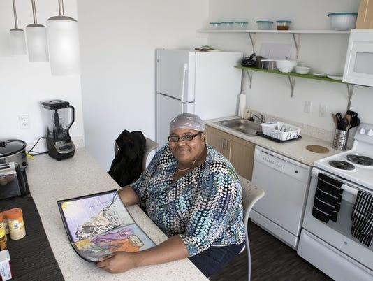 Woman poses in the kitchen of her La Mesita apartment