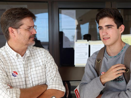 Brady Henderson (right) talks about celebrating his birthday and voting for the first time as his father, Craig, watches on Tuesday, Nov. 1, 2016, at London High School in Corpus Christi.