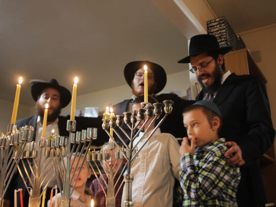 Rabbi Schneur Oirechman of Chabad Lubavich of Tallahassee, along with two of his sons and two visitors to the Temple, sing together in Hebrew following the lighting of the menorah on the first night of Hanukkah.