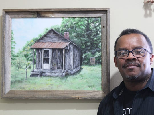 Artist Ron Smith next to a piece from his rural scenes