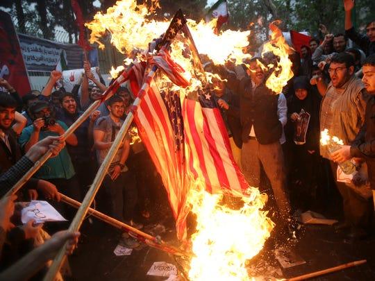 Manifestantes iraníes queman banderas estadounidenses en protesta contra Trump.