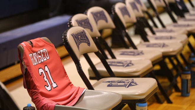 The jersey of Savannah Williams drapes a chair at the end of the bench of the Geneseo women's basketball team.  Williams, a member of the team, was killed in an auto accident late last year.