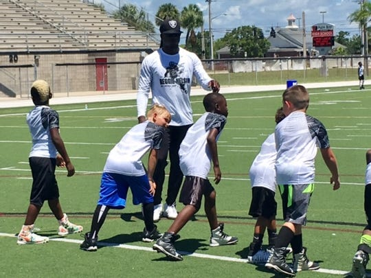 Oakland Raiders cornerback instructs children at the Reggie Nelson Football Camp at Palm Bay High.