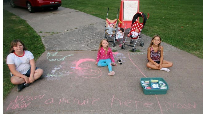 McKenzie Gillette, left, Akasha Warren, center, and Arianna Naegele pose Sept. 16 with the driveway chalk artwork they drew to brighten the days of people passing by Naegele's Sherrill home.