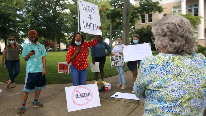 Alexsis Vinson gives information about why she and others protest to Vallery McCoy on the courtsquare in Shelby on Thursday.
