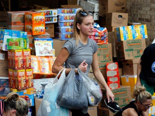 Volunteer Nicole Kaspar organizes clothing items as