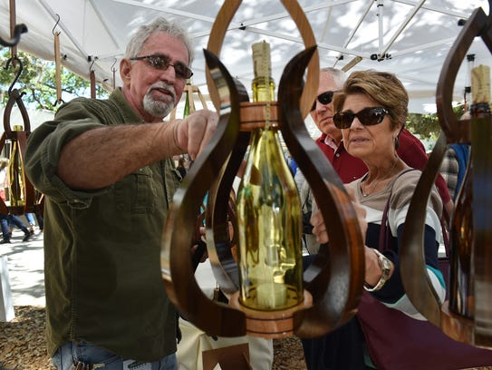 Craftsman John Smith (left), of Woodsmith of Naples, explains his creations of centerpiece lanterns made with exotic woods, priced from $45 to $335, to Tom and Julie Nowak, of Vero Beach, during the opening day of the 67th annual Under the Oaks, Fine Arts & Crafts Show on Friday, March 9, 2018, at Riverside Park in Vero Beach.