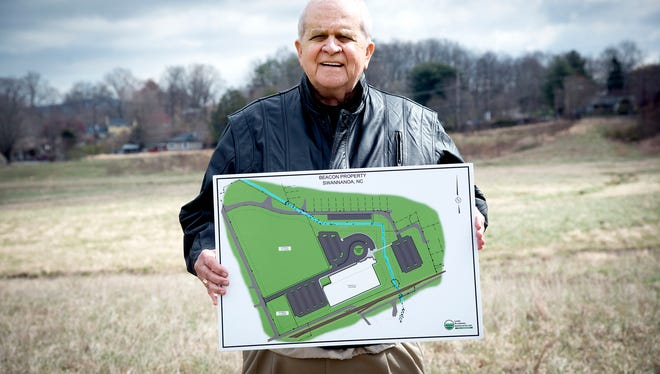 Long-time youth sports supporter Carl Bartlett holds a schematic of a youth sports complex that he and others are proposing for the old Beacon site, behind him.