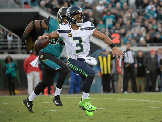 Seattle Seahawks quarterback Russell Wilson (3) scrambles as he is pressured by Jacksonville Jaguars defensive end Dawuane Smoot, left, during the first half of an NFL football game, Sunday, Dec. 10, 2017, in Jacksonville, Fla. (AP Photo/Phelan M. Ebenhack)
