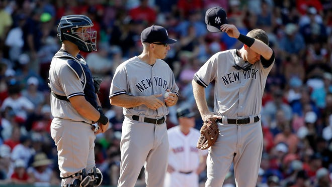 New York Yankees' Gary Sanchez, left, manager Joe Girardi, center, and Todd Frazier, right, stand on the mound during a pitching change in the sixth inning of baseball game, Sunday, Aug. 20, 2017, in Boston. The Red Sox won 5-1. Yankees' Aroldis Chapman relieved Adam Warren after Warren gave up a run in the sixth inning.
