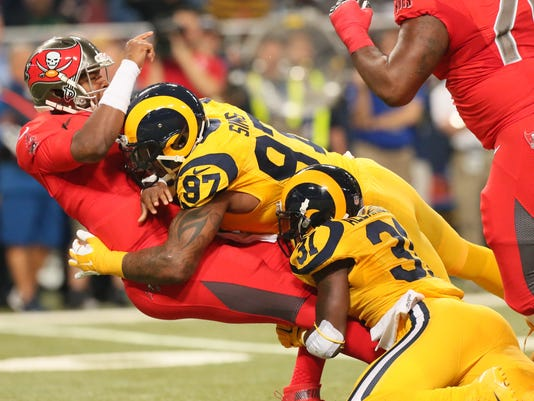 St. Louis Rams safety Maurice Alexander, lower right, and defensive end Eugene Sims force Tampa Bay Buccaneers quarterback Jameis Winston into an intentional grounding penalty during the first quarter of an NFL football game Thursday, Dec. 17, 2015, in St. Louis. The Rams won 31-23. (Chris Lee/St. Louis Post-Dispatch via AP)