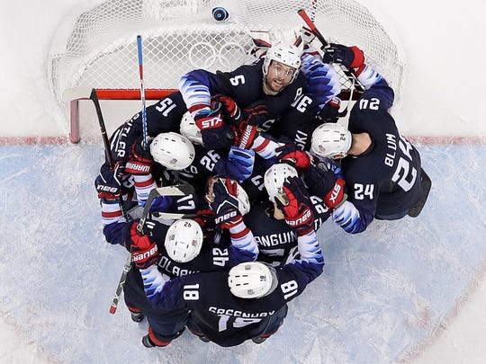 Players from the United States celebrate after the preliminary round of the men's hockey game against Slovakia at the 2018 Winter Olympics in Gangneung, South Korea, Friday, Feb. 16, 2018. The United States won 2-1. (AP Photo/Frank Franklin II)