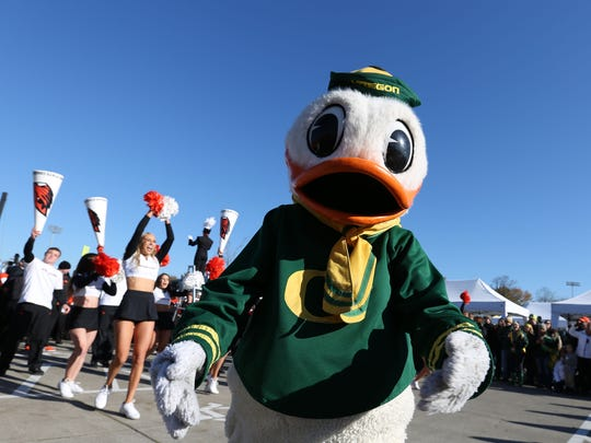 The Oregon Duck watches as Oregon State University cheerleaders face off with University of Oregon cheerleaders prior to Civil War Friday, Nov. 27, 2015, at Autzen Stadium in Eugene, Ore.