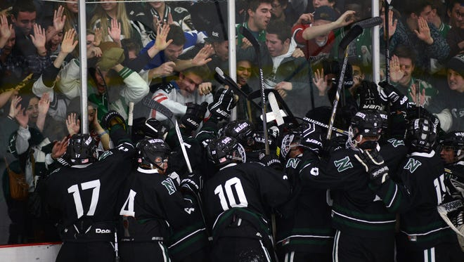 Novi players jump; for joy on the glass with their fans following a 4-2 win Friday over rival Northville at Novi Ice Arena.