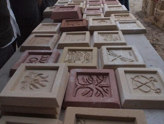 An array of 5-by-5-inch molds with designs scratched