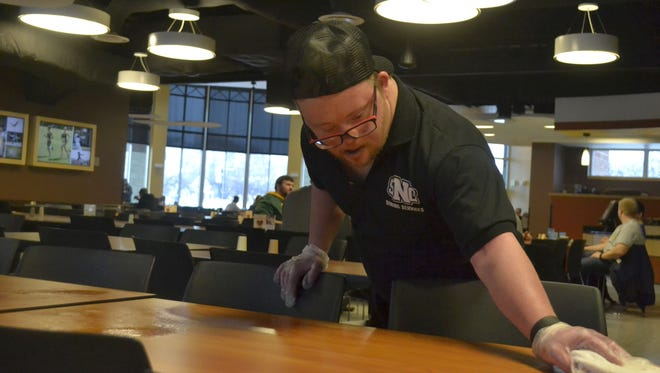 Steve Pyne, a Dining Services worker at St. Norbert College, cleans a table at lunchtime in the Michels Commons dining room at the De Pere college on Wednesday, Jan. 25, 2017. Pyne, who has Down syndrome, plans to attend the Night to Shine prom for individuals with special needs Feb. 10 at Green Bay Community Church in Howard.