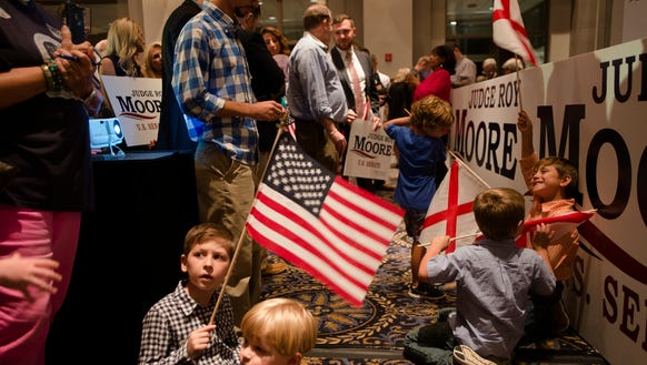 Children plat with flags while awaiting Roy Moore's