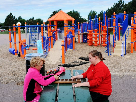 Savanna Fetters, 12, plays mancala with Taryn Hogarth, a playground leader with Sioux Falls Parks and Recreation, on the playground at John F. Kennedy Elementary School in Sioux Falls, S.D.