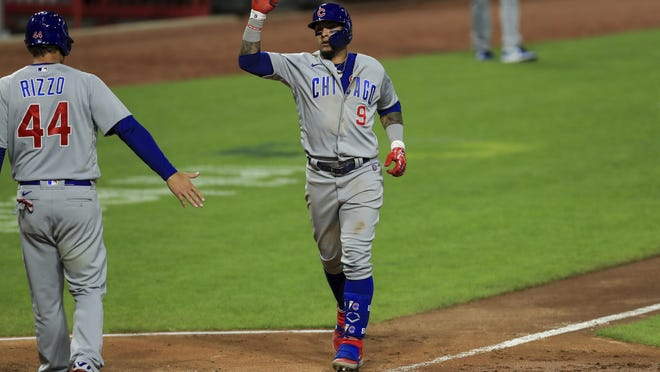 Chicago Cubs' Javier Baez (9) reacts with Anthony Rizzo (44) after hitting a two-run home run in the ninth inning during a baseball game against the Cincinnati Reds in Cincinnati, Tuesday, July 28, 2020.