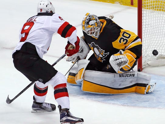 New Jersey Devils' Taylor Hall (9) puts the puck behind
