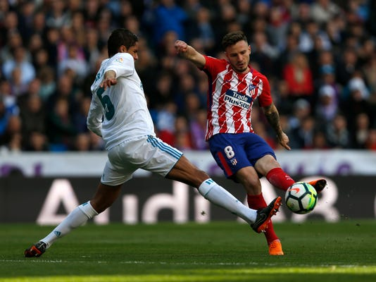 Atletico Madrid's Saul Niguez, right, vies with Real Madrid's Varane during the Spanish La Liga soccer match between Real Madrid and Atletico Madrid at the Santiago Bernabeu stadium in Madrid, Sunday, April 8, 2018. The match ended in a 1-1 draw. (AP Photo/Francisco Seco)