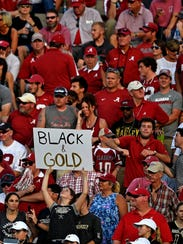 A lone Vanderbilt fan sits alone in a sea of Crimson
