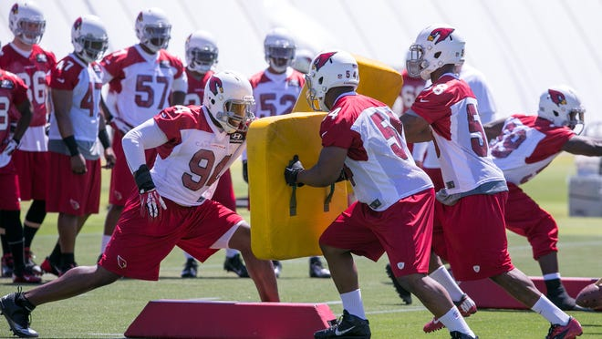Cardinals teammates hold pads for linebacker Sam Acho (left) to hit during a practice drill during Arizona's organized team activities on Tuesday.