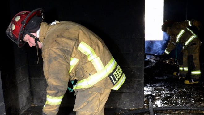 LFD recruit firefighter Lance Dillman assists in the overhaul of the burn building following an exercise. The Louisville Fire Department's Recruit Class #182 trains at the KY Regional Fire Training complex in Fern Creek on Friday. The class of 40 graduates on April 4th.