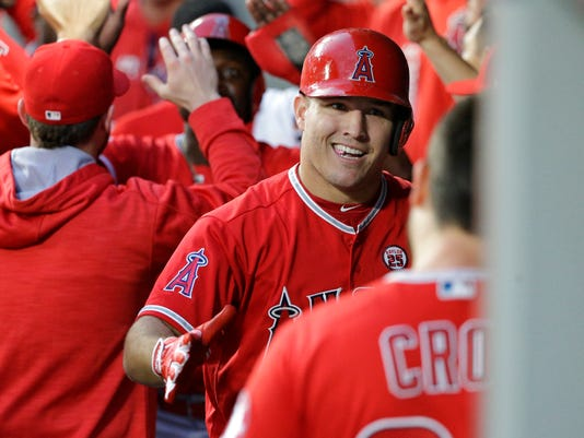 Los Angeles Angels' Mike Trout greets teammates in the dugout after he and Brandon Phillips scored on a single by Justin Upton during the first inning of a baseball game, Friday, Sept. 8, 2017, in Seattle. (AP Photo/Ted S. Warren)