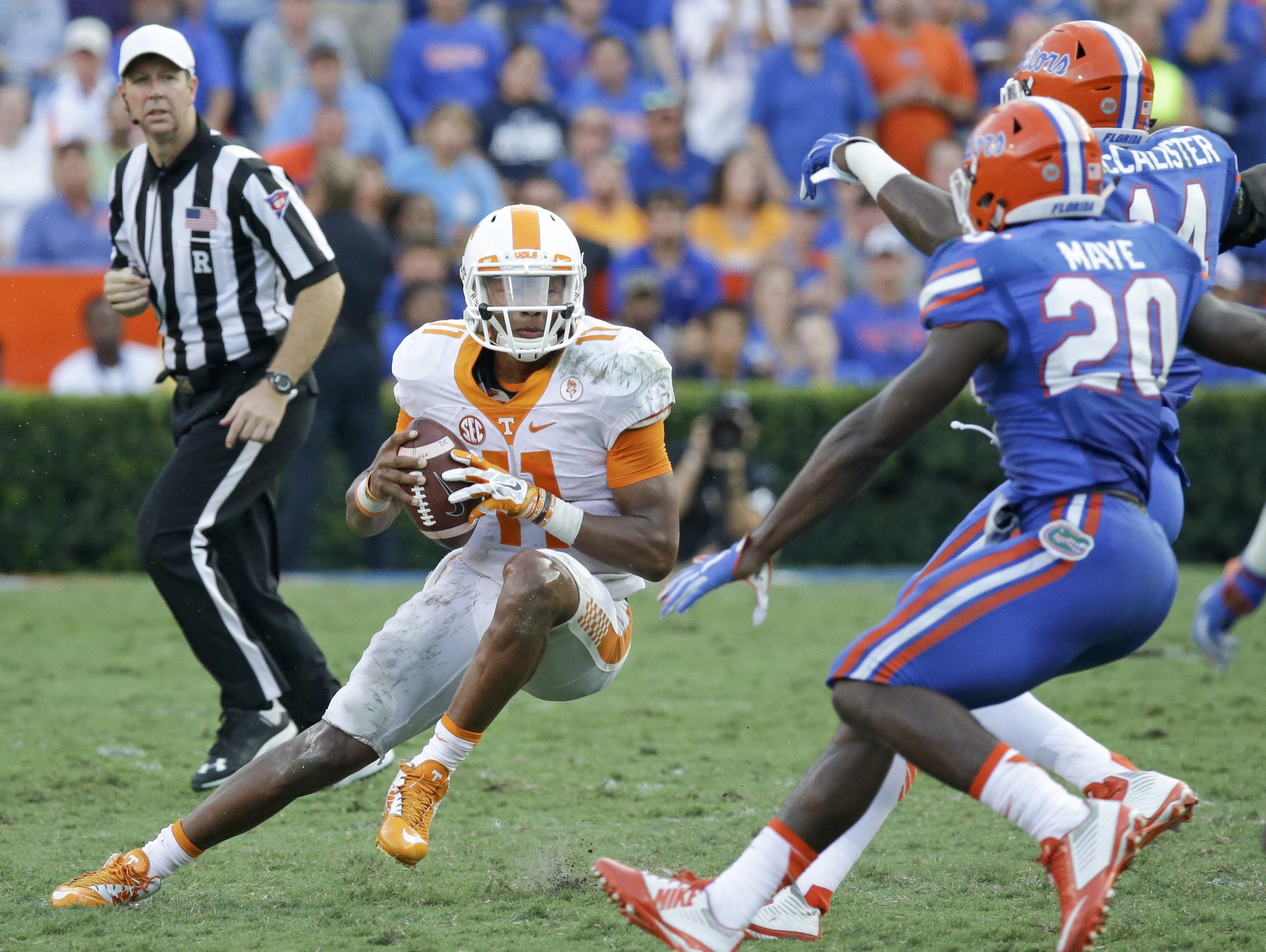 Tennessee quarterback Joshua Dobbs (11) tries to reverse his run as he is pressured by Florida defensive back Marcus Maye (20) and defensive lineman Alex McCalister (14) during the second half Saturday in Gainesville, Fla.