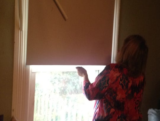 Vickie White examines damage to a living room wall