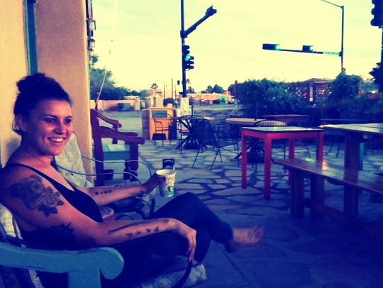 Kaleigh Jones, owner of The Bean, sits on the patio